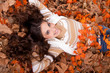 beautiful woman lying on autumn leaves