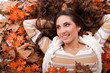smiling girl lying on autumn leaves