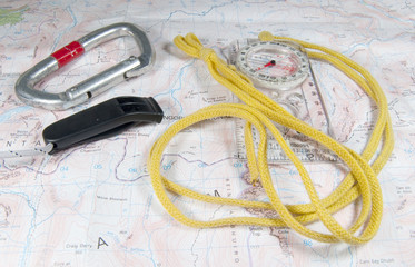 whistle, karabiner and compass on map