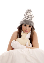 Young woman shivering in bed to keep warm