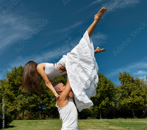 Young beautiful couple dance and embrace on grass over sky