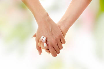 Two woman holding hands