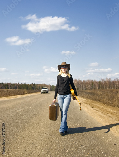 Девушка с чемоданом и гитарой идет по дороге, фото 2142324.