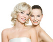 Two happy beautiful women posing on white background