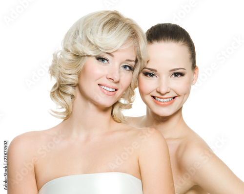 Two happy beautiful women posing on white background