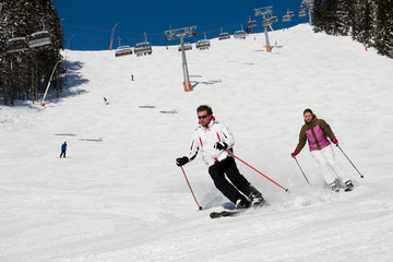 Two skiers downhill skiing in alps