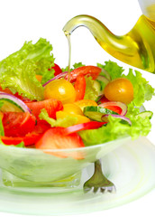 Fresh vegetable salad with olive oil pouring from bottle on whit