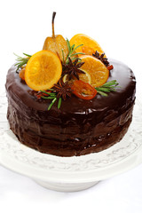 beautiful chocolate cake with glazed fruit isolated on a white b