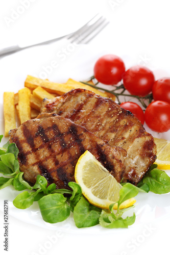 Closeup of grilled steak with lemon on white isolated background