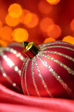 christmas decorative balls on red silk against blurred lights on