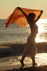 woman with red handkerchief is on beach. sunlight glare on water