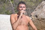 Man pretending to Smoke a Coral on a Beach poster