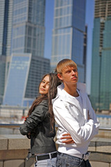 Two fashionable and trendy teenagers against and skyscrapers