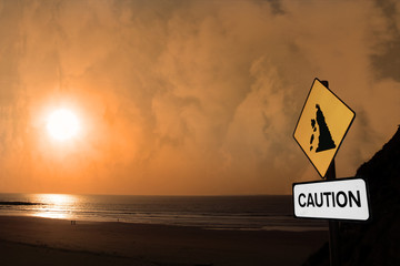 beach landslide caution sign at sunset