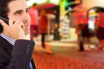 Young businessman talking on cellular phone at the street
