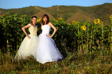 Girls in wedding dresses in sunflowers
