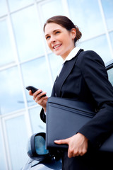 Young business woman outside with mobile phone, smiling