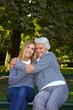 Oma umarmt Enkelin im Park