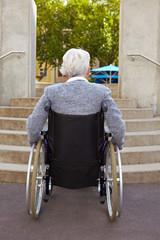 Rollstuhlfahrerin vor Treppe