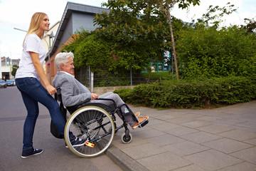 Frau hilft Rollstuhlfahrerin über Bordstein