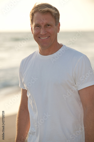 attractive blond man in white tshirt on the beach