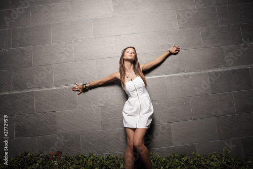 Woman with arms outstretched on the wall