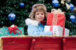 Little girl with Christmas presents in Santa Claus sledge