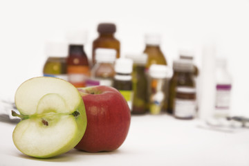 green and red apples in front of many pills and pill