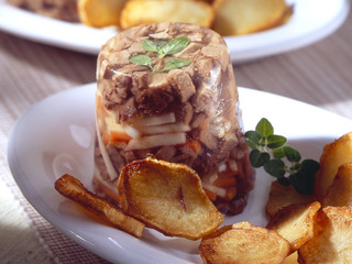 Goose aspic on a white plate with potatos.