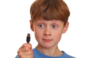 Irritierter Junge schaut auf einen USB-Stecker