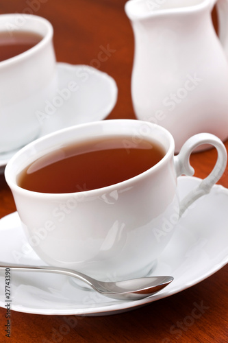 Black tea in mugs with saucers