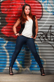 Young Hispanic Woman in Urban Lifestyle with Graffiti Background poster