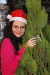 YOUNG SMILING SANTA WOMAN NEAR CHRISTMAS TREE