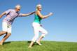 Senior couple running through field