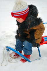 a little girl sitting in her sledge and wondering how it works