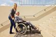 Frau schiebt Rollstuhlfahrerin Treppen hoch