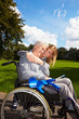 Enkelin redet mit Oma im Rollstuhl