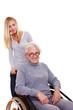 Enkelin schiebt Oma im Rollstuhl