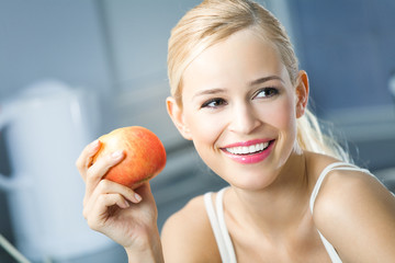 Portrait of young happy smiling woman with apple at home