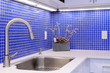 Kitchen sink, white counter with chrome faucet and blue tile wal