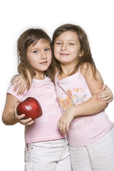 two girls, twins holding in his hand a red big apple