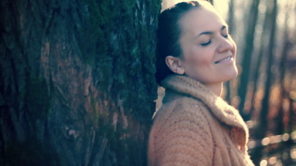 Happy attractive woman standing by the tree, steadicam shot