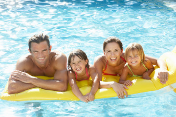 Young family, parents with children, in pool