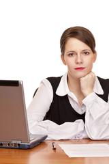 dynamische ernste Geschäftsfrau sitzt in Büro am Schreibtisch