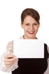 Junge lachende Frau hält leere Karte in Kamera