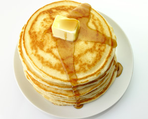 Golden pancakes with butter and maple syrup.