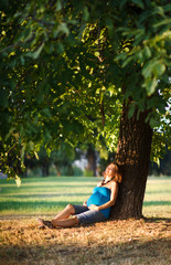 Beautiful pregnant woman sitting under a tree in park