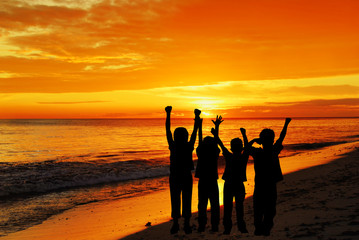 Childrens silhouettes on a sunset beach