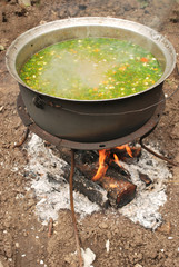 fish soup (with parsley) on fire outside