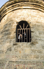 Teen girl looks out of the jail window